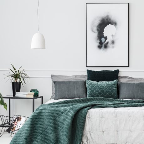Emerald green pillows and blanket on bed in elegant bedroom interior with plant and poster on white wall